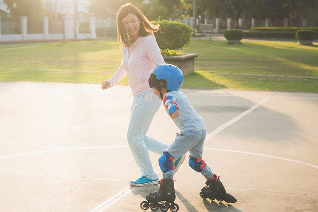 Young woman holding hand with boy rollerblading